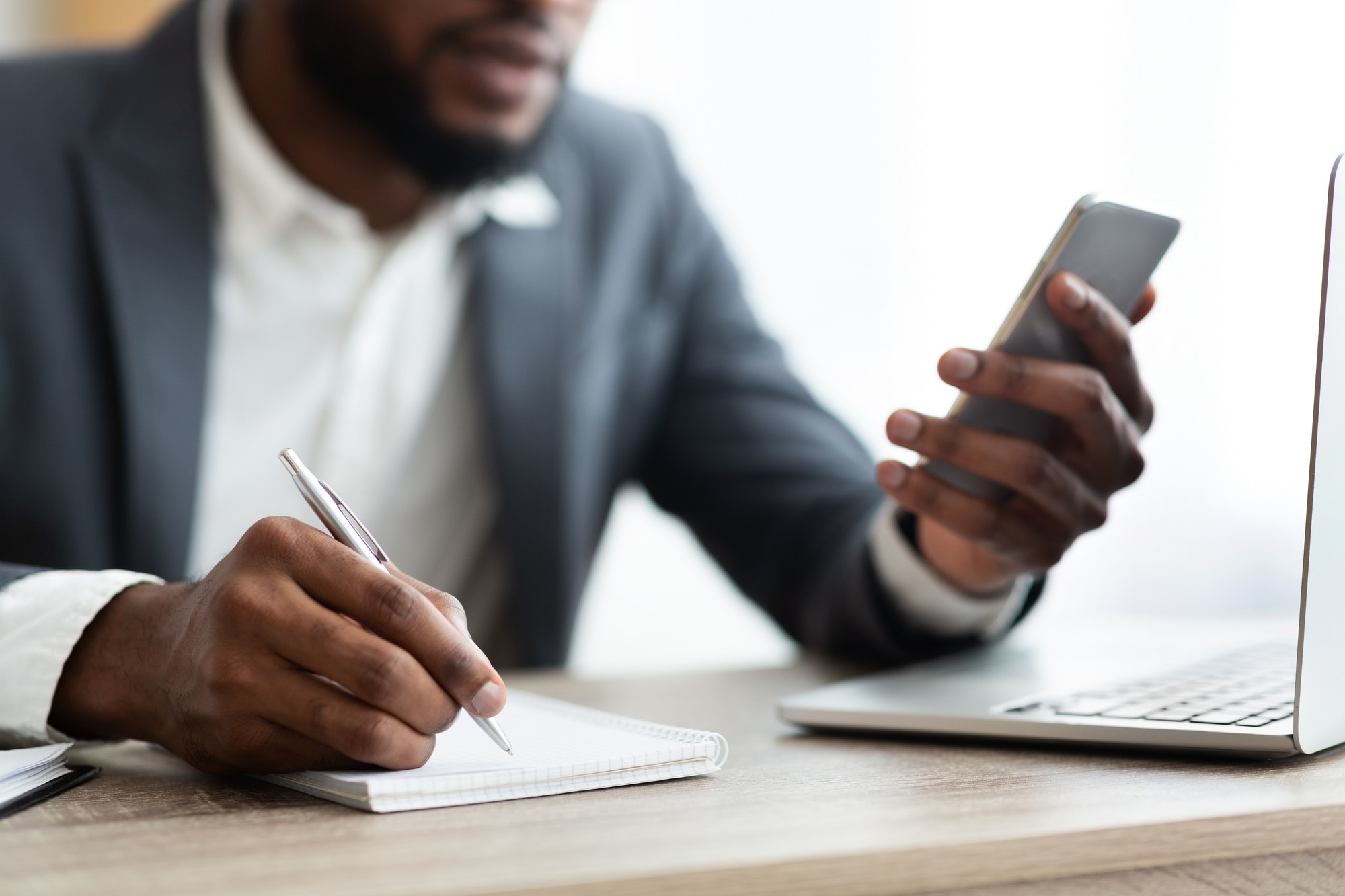 African American employer using smartphone and taking notes in office