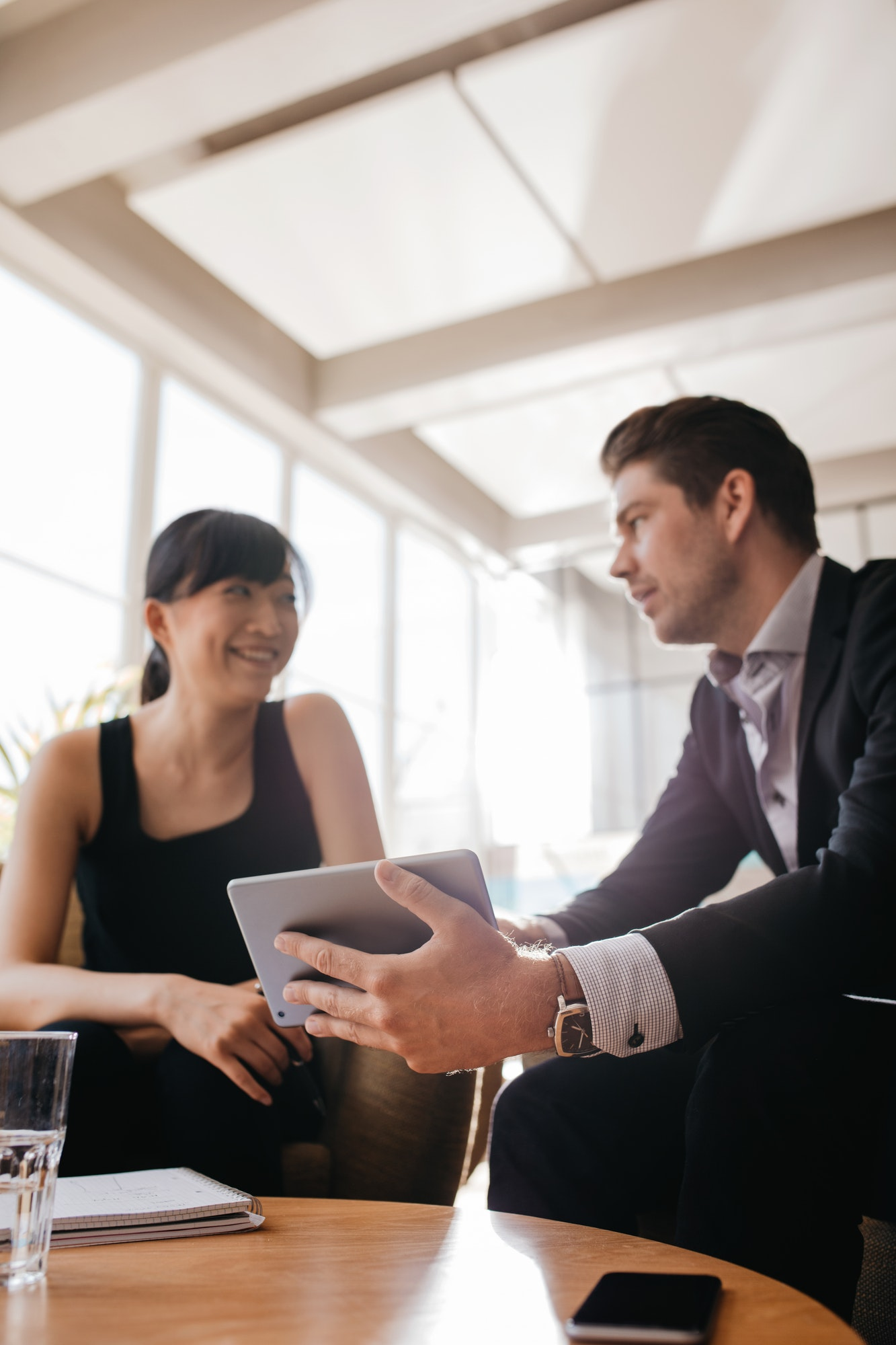 Businessman showing presentation to female colleague on tablet